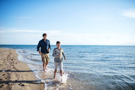 Father with small son on a walk outdoors on beach, running in water.