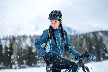 Female mountain biker standing outdoors in winter nature. 免版税图像