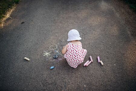 A rear view of cute toddler girl outdoors in countryside, chalk drawing on road.