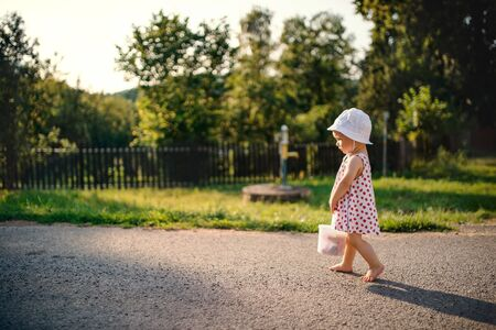 A cute toddler girl walking outdoors on road in countryside in summer.