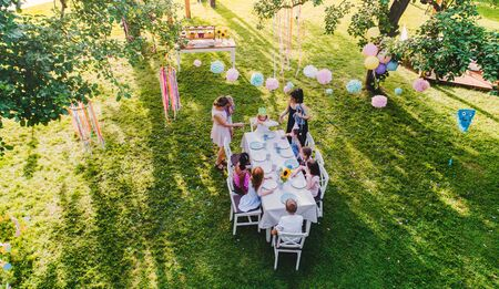 High angle view of small children sitting at the table outdoors on garden party.