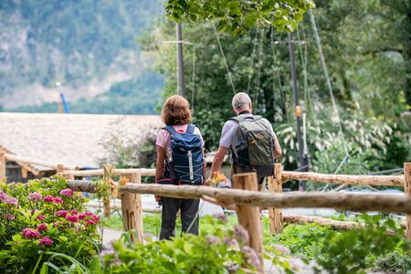A rear view of senior pensioner couple hiking, walking. Stock fotó