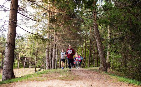 Gran grupo de personas de varias generaciones que corren una competencia de carreras en la naturaleza.