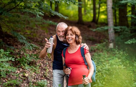Senior tourist couple with backpacks on a walk in forest in nature. Stock fotó