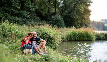 Senior tourist couple with backpacks on a walk in nature, sitting by lake.