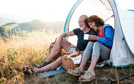Senior tourist couple in love sitting in nature at sunset, resting.