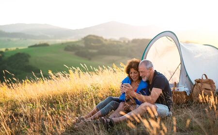 Senior tourist couple with smartphone sitting in nature at sunset, taking selfie. Stock fotó