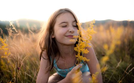 A portrait of small girl in grass in nature, holding flower.
