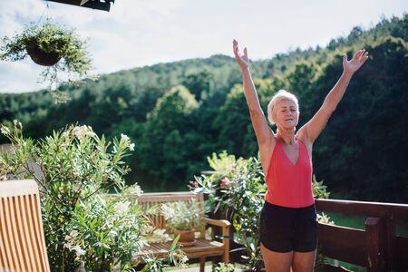A senior woman standing outdoors on a terrace in summer, doing exercise. Stok Fotoğraf