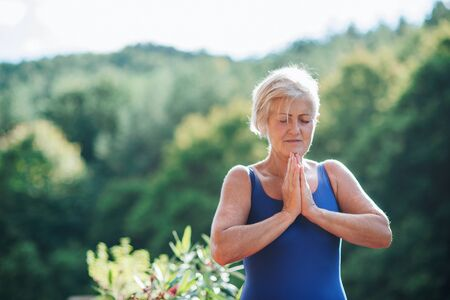 A senior woman standing outdoors on a terrace in summer, doing yoga exercise. Stok Fotoğraf