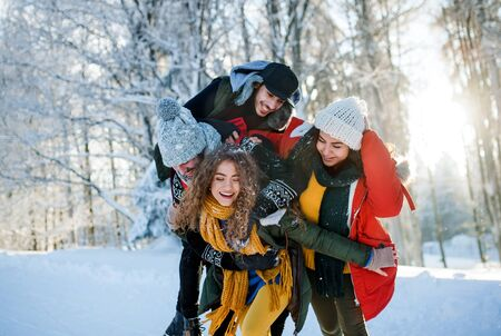 Group of young friends on a walk outdoors in snow in winter forest, having fun. Stock fotó