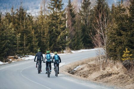 Rear view of mountain bikers riding on road in mountains outdoors in winter.