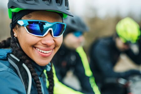 Female mountain biker with friends standing on road outdoors in winter. Stock fotó