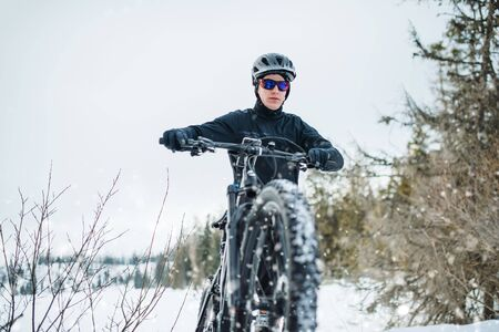 Front view of mountain biker riding in snow outdoors in winter nature.