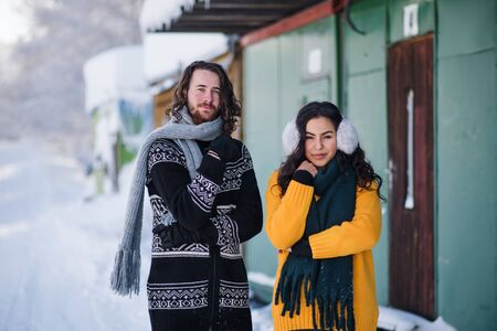 A portrait of couple standing outdoors in winter, looking at camera.