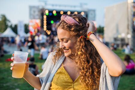 A young woman with drink dancing at summer festival. Stock fotó