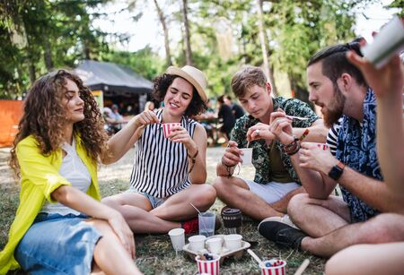 Group of young friends at summer festival, sitting on the ground and eating. Stock fotó