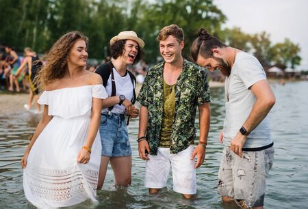 Group of young friends at summer festival, standing in lake.