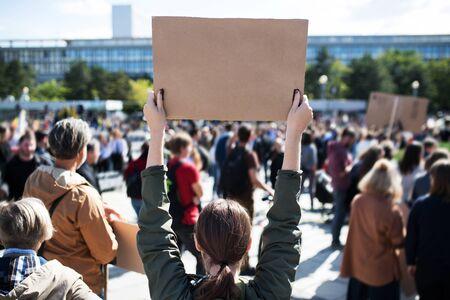 Achteraanzicht van mensen met borden en posters over wereldwijde staking voor klimaatverandering. Stockfoto