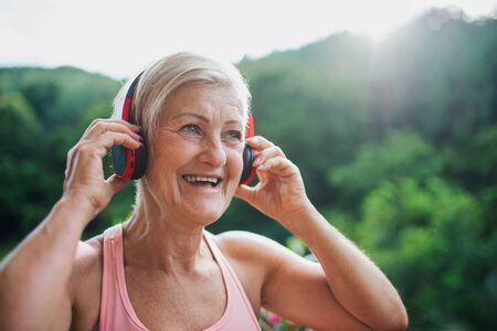 A senior woman with headphones standing outdoors on a terrace in summer. Stok Fotoğraf