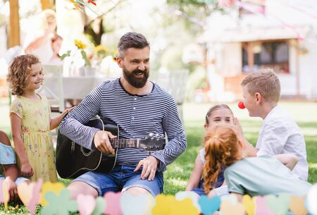 Man with small children sitting on ground outdoors in garden in summer, playing.