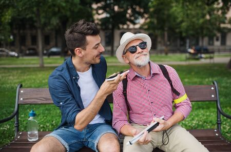 Young man and blind senior sitting on bench in park in city, using smartphone. Reklamní fotografie