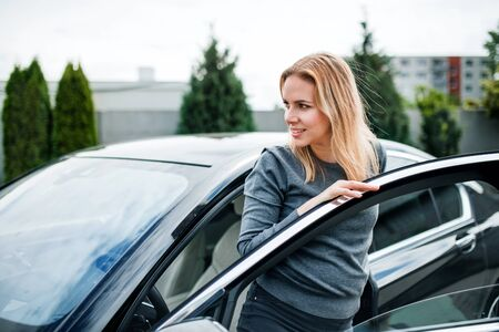 Young woman getting out of car in town. Reklamní fotografie