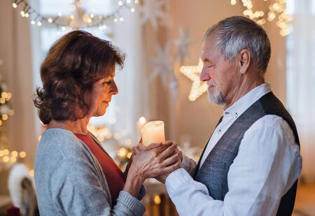 Side view of happy senior couple indoors celebrating Christmas.
