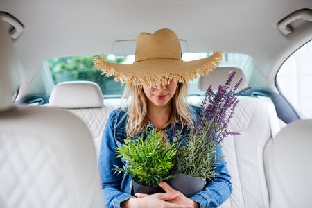 Young woman with hat and plants sitting in car, having fun.