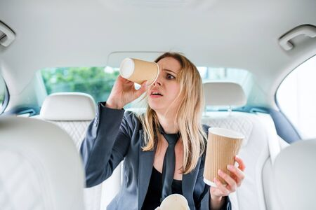 Young frustrated woman with empty paper glasses sitting in car.