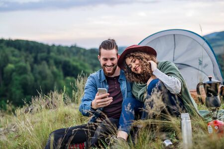 Young tourist couple travellers with tent shelter sitting in nature, using smartphone.