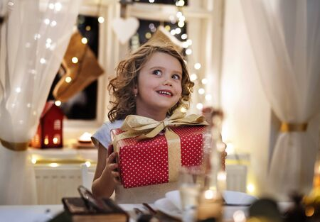 Cheerful small girl sitting indoors at Christmas, holding present. Stock fotó