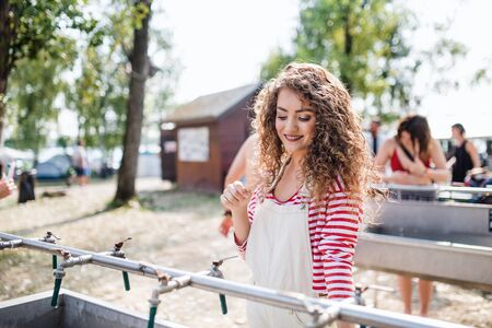 Young woman with tootbrush at summer festival, washing in the morning.