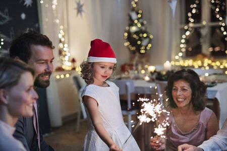 Small girl with parents and grandparents indoors celebrating Christmas. Stock fotó