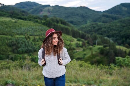 Young tourist woman traveller with backpack walking in nature.