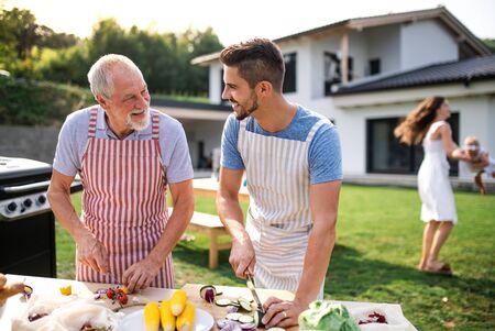 Portret van vader en zoon buitenshuis op tuinbarbecue, grillen. Stockfoto