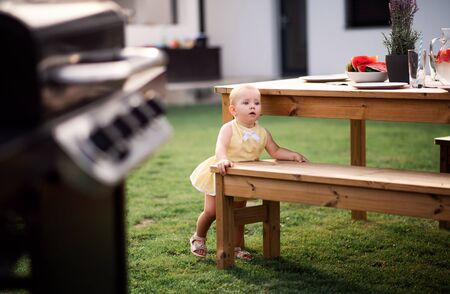 Small girl standing outdoors on family garden barbecue.