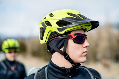 Two mountain bikers with sunglasses standing on road outdoors in winter. Stock fotó