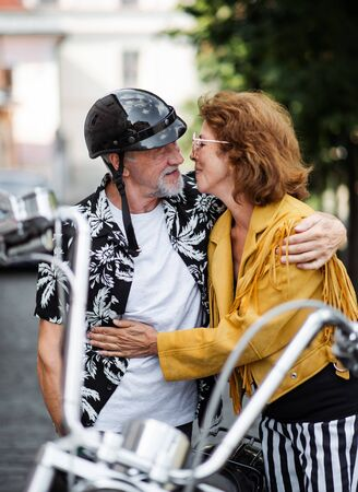 A cheerful senior couple travellers with motorbike in town, kissing.