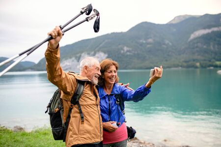 A senior pensioner couple standing by lake in nature, taking selfie. Stock fotó