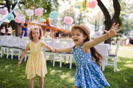 Małe dziewczynki biegają na świeżym powietrzu w ogrodzie latem, koncepcja obchodów urodzin. Zdjęcie Seryjne