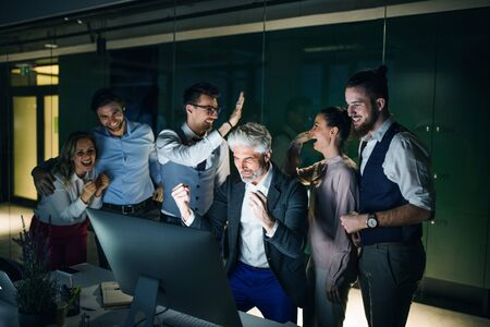 A group of business people with computer in an office, expressing excitement. Stock fotó