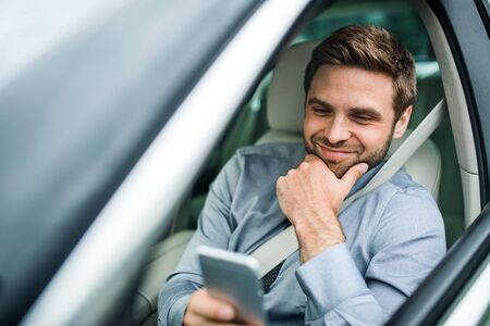 Young businessman with shirt, tie and smartphone sitting in car. Stock fotó