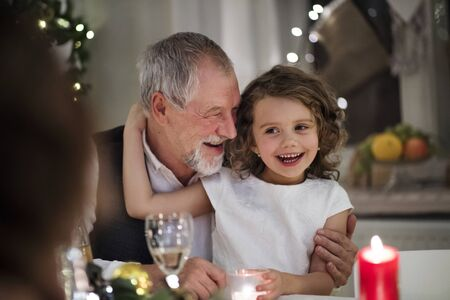 Senior grandfather with small granddaughter indoors at Christmas, sitting at table. Stock fotó
