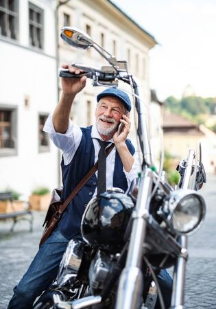 A senior businessman with motorbike in town, using smartphone. Stock fotó