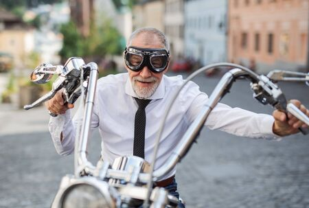 A front view of senior businessman with goggles and motorbike in town.