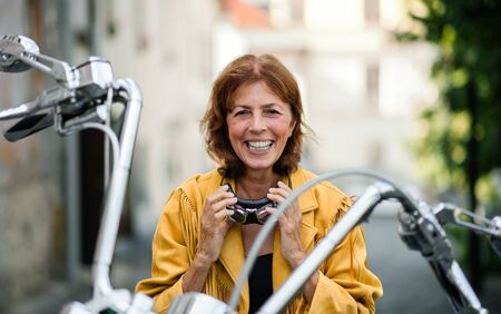 Cheerful senior woman traveller with motorbike in town.