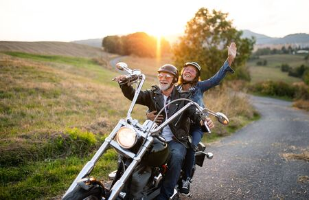A cheerful senior couple travellers with motorbike in countryside.
