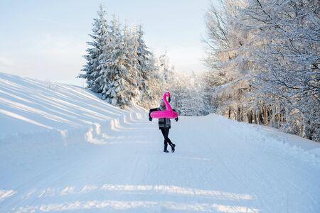 Jeune homme à l'extérieur dans la neige dans la forêt d'hiver, s'amusant. Banque d'images