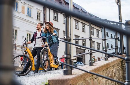 Young tourist couple travellers with electric scooters in small town.